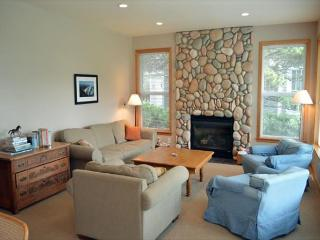 Lower level living room with stone gas fireplace, couch, three arm chairs and large picture windows providing spectacular golf course views.