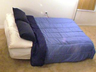 Full sized futon made up into a bed.