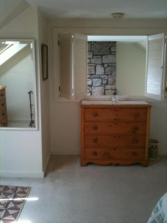 Upstairs bedroom, with louvered window to cathedral ceiling over living room