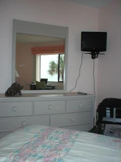 Master bedroom has wall mounted TV; huge window allows view of beach and sparkling water of the Gulf