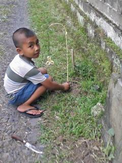Youngster practicing making a 'penjor'
