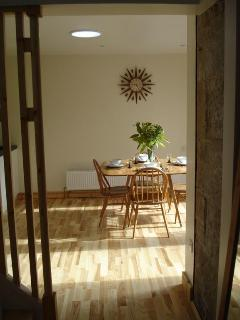 The kitchen from the hall way - the vintage ercol table and chairs and original sunburst clock clearly visible
