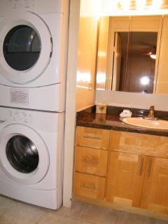 New Full Size High Effieciency Whirlpool Duet Washer & Dryer next to Bath Vanity & Mirror