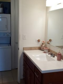 Bath vanity with washer/dryer in background
