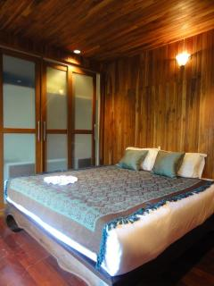 Rich wood bed room with King size bed in modern Thai style.