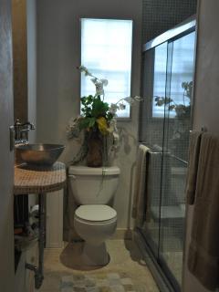 Second bathroom featuring unique stone tile accents