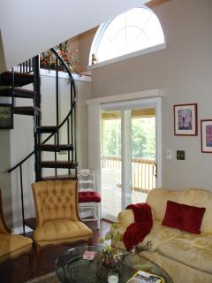 Living room and Spiral Staircase to Loft Bedroom. Sliding glass doors to Screened in Porch.