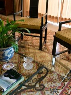 Elegant seating in the dining room, with glass and wrought iron table that shows off the tile floor