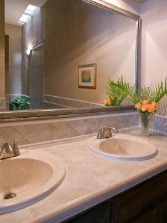 Clean and spacious master bathroom with two sinks and huge mirror...