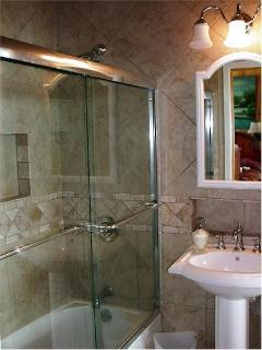 Bathroom adjoining downstairs Queen Bedroom features a pedestal sink and tub with shower.