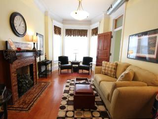 Brown Line Flat (Second Floor), Living room with lots of comfy seating and beautiful bay windows.