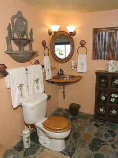 Bathroom has stone floors & hammered copper sink set in hand-carved base.