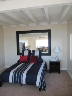Main Bedroom with a comfortable queen bed and a large mirror reflects the ocean!