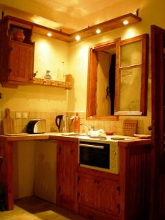 The open plan kitchen is small but fully functional with oven, hob, sink, and full size fridge