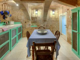 Kitchen/dining room in cellar with crossed stone arches.