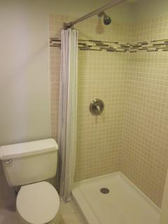 Light and open  master bathroom with walk-in shower and tile surround.
