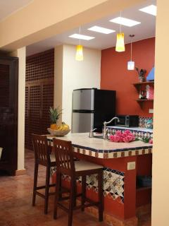 Bright kitchen with modern appliances, a breakfast island... all covered with Talavera tiles