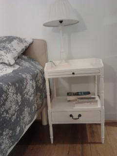 Lamp and bedside table match the rest of the decoration