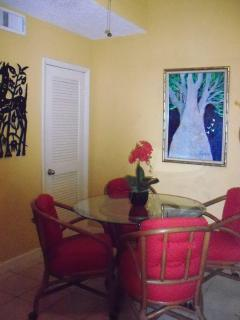 Entry with original art on walls and bar cart to left