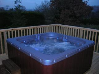 HOT TUB on decking area at night.