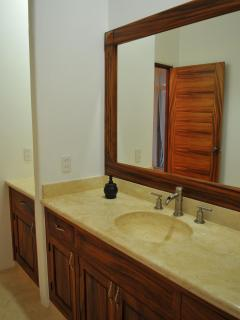 Bathroom No. 2 with roomy cabinets and large mirror and shower.