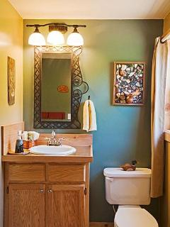 Upstairs full bathroom with stainless countertops and pottery collage decoration