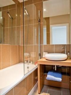Bathroom, tiled, with large mirrors and strong shower and bath. Towels, gels etc