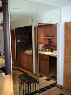 mirrored wall and doorway between dining room and kitchen