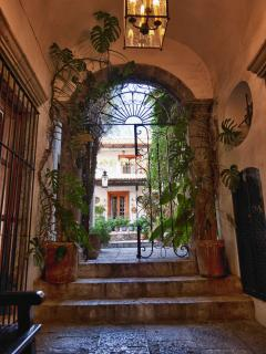 Arched foyer entrance, wrought-iron gate, orchid- and fern-lined, stone-paved walkway, central patio