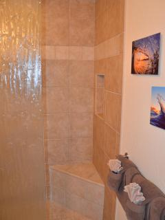 Tiled shower with bench in the master.