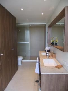 Ensuite bathroom featuring double sink and enormous walk-in shower