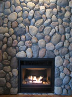 Cozy Living Room with beautiful River Rock wall surrounding gas fireplace