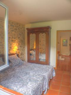 The downstairs bedroom features twin beds and a view of the large garden