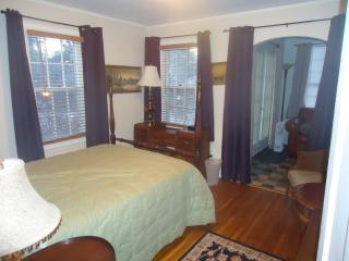 First floor bedroom adjacent to bathroom and looking toward sun room with French doors to gardens.