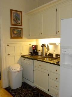 Adjacent, and behind kitchen is a service kitchen, with another dishwasher, sink, and refrigerator, along with storage.