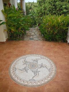 Dolphin mosaic in tiles, path to pool beyond