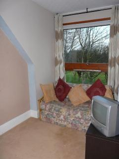 The sitting area of bedroom 1, with sofabed giving extra sleeping space in this family bedroom