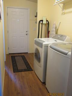 Laundry area with iron, ironing board, full size washer and dryer