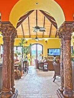 Carved tropical columns grace the passage between living room and kitchen