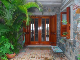 A welcoming entrance to our charming villa, with island stone work and mahogany all around.