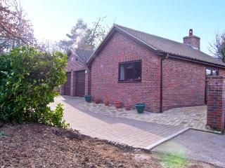 THE OAKS, ground floor accommodation, king-size bedroom, woodburning stove in Wa