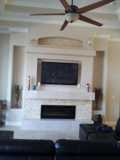 Living room with fireplace/TV wall. Watch the game while overlooking pool, lanai & lagoon