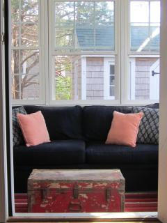 Enclosed porch of kitchen leads to back deck