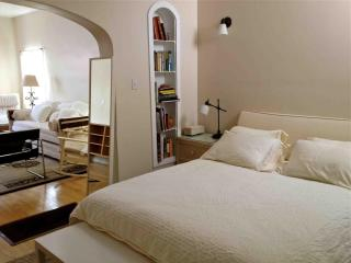 Bedroom area is cozy nook with shelves stocked with electic selection of books on L.A. living/style.