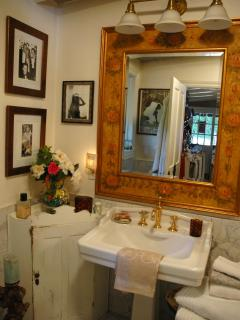Enjoy a lovely light filled bathroom with marble floors and large mirrors