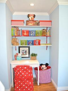 Nook in kids room with desk, drawing supplies, books, blocks, stuffed animals, board games and toys
