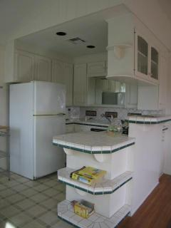 Kitchen with gas stove is open to living room