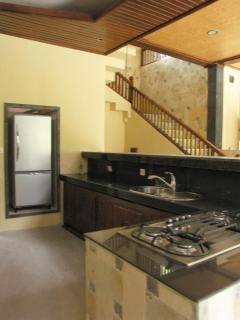 The kitchen with stairs to the bedroom in the background.