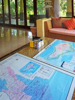 The living room coffee table serves as a trip planner: guide books, maps of the province and Bali.