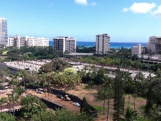 View from studio window showing parking lot  and park across the street and Waikiki beach beyond.